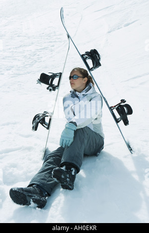 Young female skier sitting on the ground under skis, looking away - Stock Photo