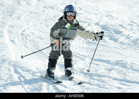 Boy skiing down hill, full length - Stock Photo