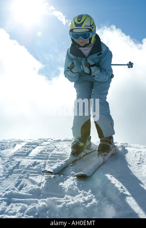 Young skier standing on top of hill, looking at camera, full length portrait - Stock Photo