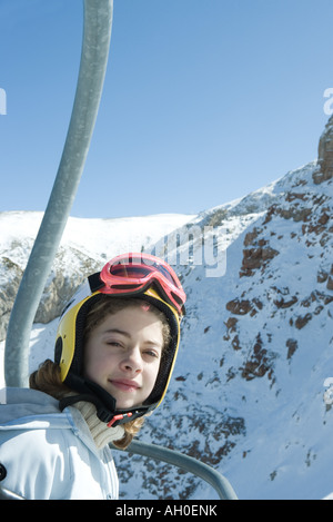 Teenage girl in chair lift, dressed in ski clothing, smiling at camera - Stock Photo