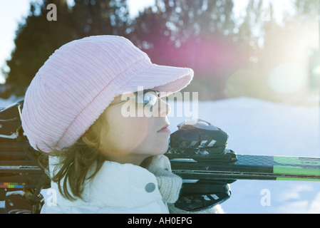 Young female skier holding skis on shoulder, side view, looking away - Stock Photo