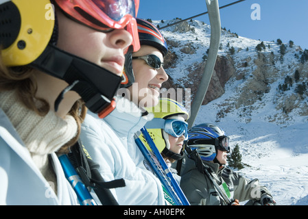 Four young skiers riding ski lift, side view, close-up - Stock Photo