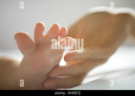 Cropped view of adult hand touching baby's foot, close-up - Stock Photo