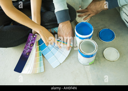 Couple sitting on floor, pointing to color swatches, cropped view - Stock Photo