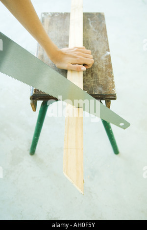 Woman sawing wood with saw, cropped view of hand - Stock Photo