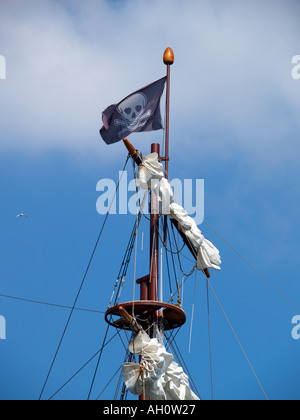 Skull and bones jolly roger pirates flag waving in the mast of a tall ship - Stock Photo