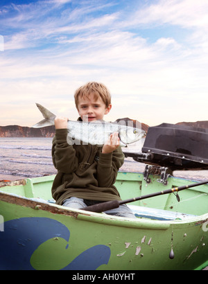 boy 7 with fish in boat - Stock Photo