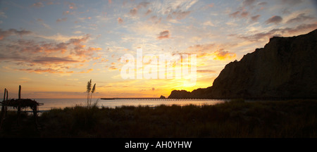 sunrise over sand dune and wharf at tolaga bay - Stock Photo