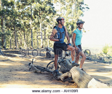 Two bikers resting in the woods - Stock Photo