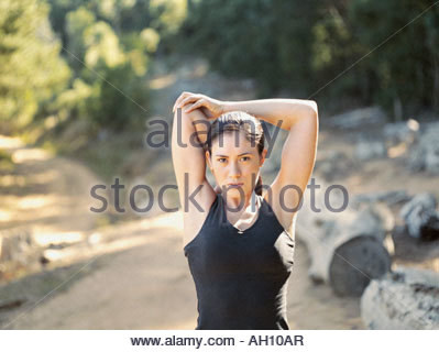A woman stretching her arms out in the woods - Stock Photo