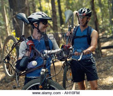 Two men carrying their bikes - Stock Photo