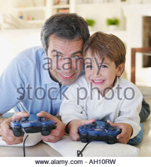Man and boy playing video games - Stock Photo
