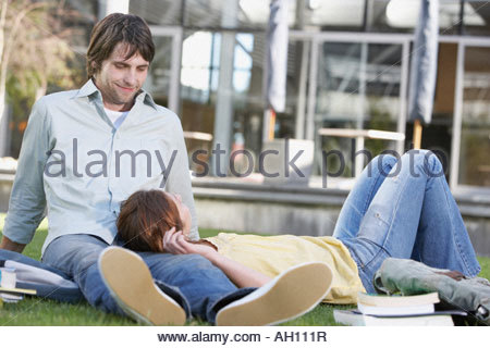 Teenage girl and boy laying down on grass with books - Stock Photo