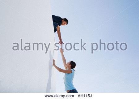 A man helping a woman climb a wall - Stock Photo