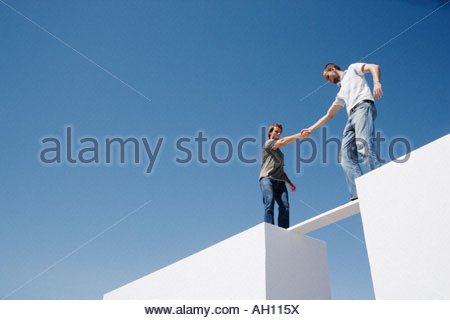 Two men atop two walls balancing on a plank - Stock Photo