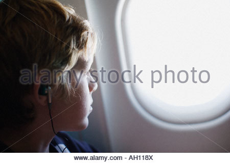 A child looking out his airplane window - Stock Photo