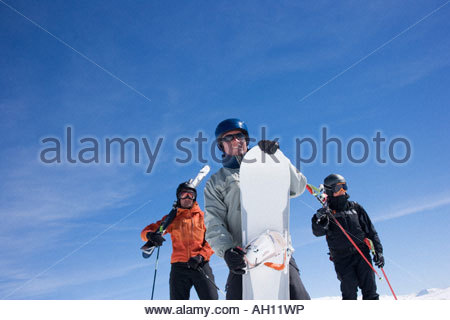 Skiers and snowboarder standing on mountain - Stock Photo