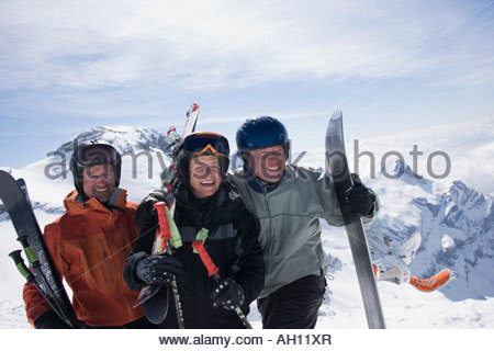 Smiling skiers on a mountain carrying their equipment - Stock Photo