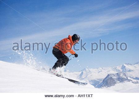 Man skiing downhill on mountain - Stock Photo