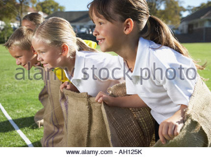 Kids potato sack racing - Stock Photo