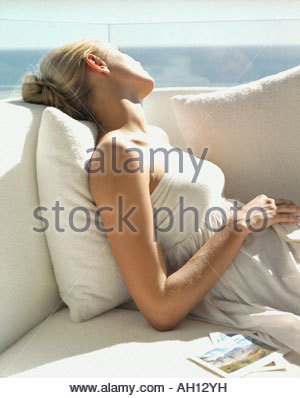 A woman lying back on a couch - Stock Photo