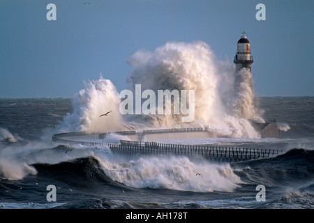 A huge wave breaks over a lighthouse on Roker Pier during a winter storm. Sunderland, Tyne & Wear. - Stock Photo