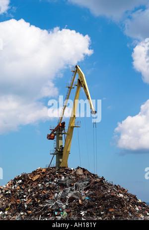 Harbour crane loading metal scrap in port - Stock Photo