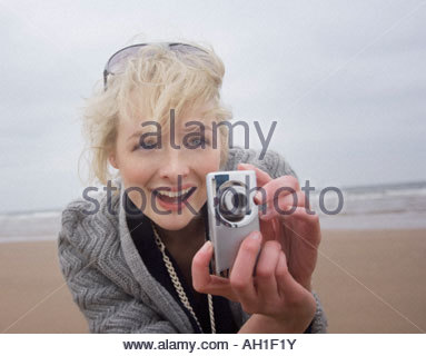 A woman taking pictures at the beach - Stock Photo