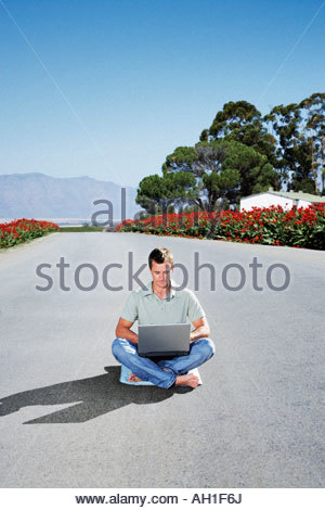 A man on a laptop in the middle of the road - Stock Photo