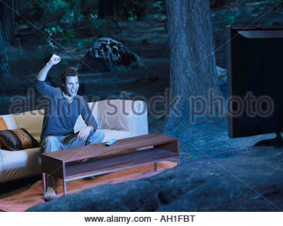 A man watching television outdoors in the woods - Stock Photo