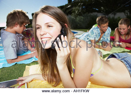 Friends hanging out by a pool - Stock Photo