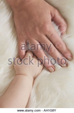 A baby's hand holding a woman's hand - Stock Photo