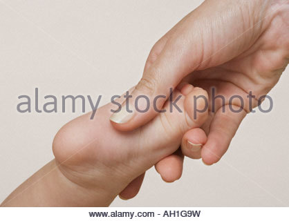 A woman's hand holding a baby's foot - Stock Photo
