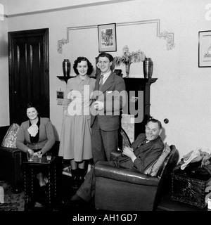 OLD VINTAGE FAMILY PHOTOGRAPH SNAP SHOT MARRIED COUPLE WITH PARENTS IN LIVING ROOM CIRCA 1950 - Stock Photo