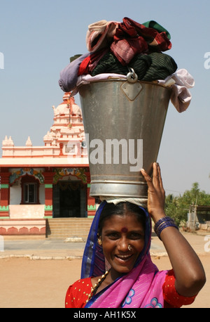 Indian lady with bucket and clothes on her head in front of a Hindu temple , Karnataka, India - Stock Photo
