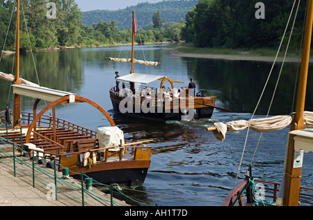Pleasure boats gabares taking tourists on a trip down the river Dordogne near the village of La Roque Gageac - Stock Photo