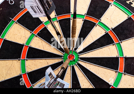 three darts stuck in a dart board - Stock Photo