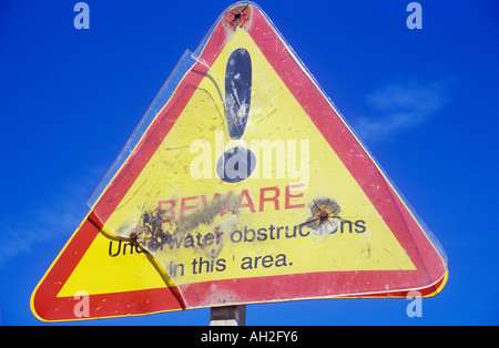 Battered triangular red yellow and black sign against bright blue sky stating Beware Underwater obstructions in - Stock Photo