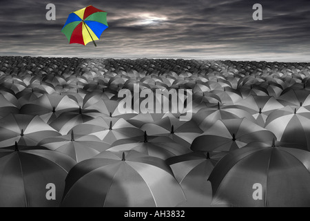 vast sea of black and white umbrellas with one coloured colored one flying away into the sky rain - Stock Photo