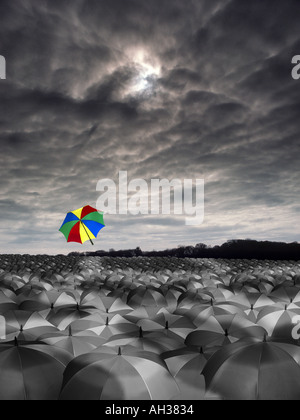 vast sea of black and white umbrellas with one cloured colored one flying away into the sky rain - Stock Photo