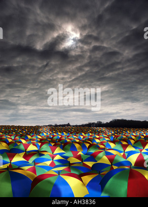 vast sea of coloured colored umbrellas with dark sky overhead rain - Stock Photo