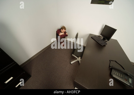 Man cowering in the corner - Stock Photo