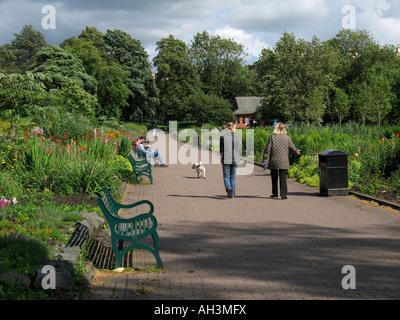 People walking a dog in Kelvingrove Park, Glasgow. - Stock Photo