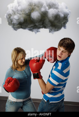 Male and female with boxing gloves under cloud - Stock Photo