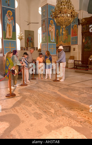 tourist and guide looking at mosaic map fall painting mural Moses Memorial Church Mount Nebo East Bank Plateau Jordan - Stock Photo