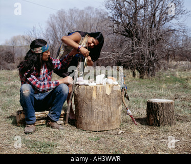 Native American Bear Carvers working on wooden logs in forest - Stock Photo