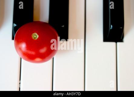 Piano keyboard close up with tomato - Stock Photo