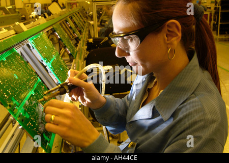Production operator soldering circuit boards at Axiom Manufacturing ...