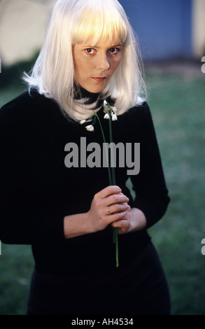 Platinum blond female dressed in black holding long stems of snowdrops flowers in her hands - Stock Photo