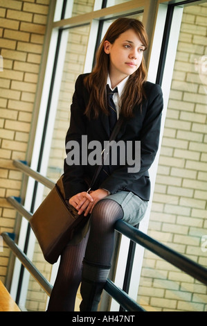 A student in uniform, seated on railing - Stock Photo